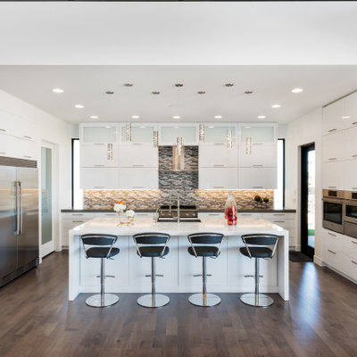 Kitchen - large contemporary l-shaped brown floor kitchen idea in Salt Lake City with an undermount sink, flat-panel cabinets, white cabinets, gray backsplash, matchstick tile backsplash, stainless steel appliances, an island and gray countertops