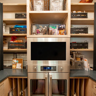 This is an example of a small country u-shaped kitchen pantry in Other with louvered cabinets, light wood cabinets, quartz benchtops, stainless steel appliances, light hardwood floors, brown floor and black benchtop.