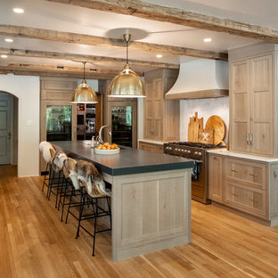 Mid-sized farmhouse eat-in kitchen photos - Example of a mid-sized country u-shaped light wood floor and brown floor eat-in kitchen design in Other with an undermount sink, shaker cabinets, light wood cabinets, quartz countertops, white backsplash, stone slab backsplash, stainless steel appliances, an island and black countertops
