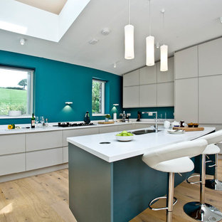 This is an example of a contemporary u-shaped kitchen in Devon with a double-bowl sink, flat-panel cabinets, white cabinets, blue splashback, light hardwood flooring, a breakfast bar, beige floors and white worktops.