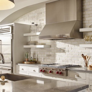 Large transitional open concept kitchen designs - Example of a large transitional open concept kitchen design in St Louis with an undermount sink, shaker cabinets, white cabinets, solid surface countertops, white backsplash, brick backsplash, stainless steel appliances and an island