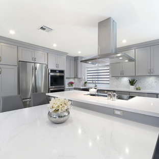 Photo of a large transitional l-shaped open plan kitchen in Miami with a farmhouse sink, shaker cabinets, grey cabinets, quartz benchtops, grey splashback, marble splashback, stainless steel appliances, porcelain floors, multiple islands and grey floor.