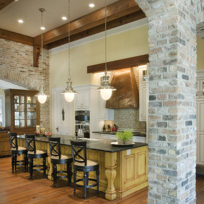 Inspiration for a timeless galley medium tone wood floor and brown floor kitchen remodel in Nashville with mosaic tile backsplash, a farmhouse sink, raised-panel cabinets, white cabinets, multicolored backsplash, stainless steel appliances and an island