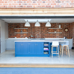 Photo of a classic u-shaped enclosed kitchen in Essex with shaker cabinets, blue cabinets, brick splashback, stainless steel appliances, an island, white floors and white worktops.