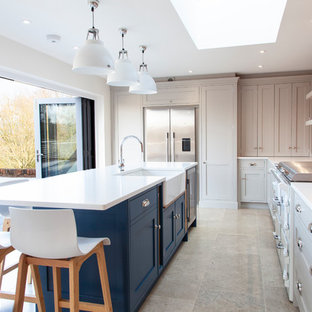 This is an example of a traditional u-shaped enclosed kitchen in Essex with a belfast sink, shaker cabinets, white cabinets, brick splashback, stainless steel appliances, an island and white worktops.