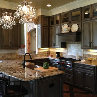 Example of a mid-sized classic u-shaped brown floor eat-in kitchen design in New Orleans with a farmhouse sink, granite countertops, beige backsplash, stainless steel appliances, a peninsula, gray cabinets and stone tile backsplash