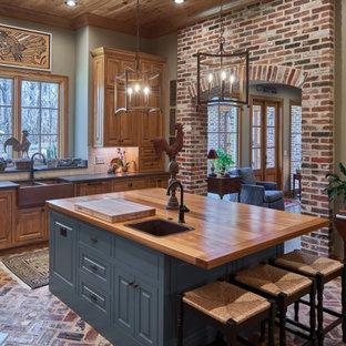 Foto på ett stort lantligt brun l-kök, med en rustik diskho, luckor med upphöjd panel, skåp i mellenmörkt trä, träbänkskiva, grått stänkskydd, tegelgolv, en köksö och flerfärgat golv