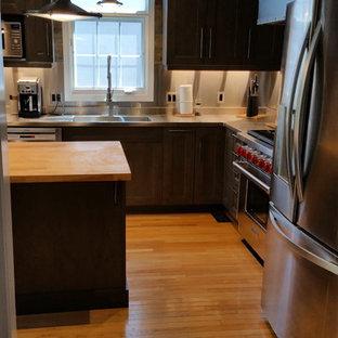 オタワの中サイズのインダストリアルスタイルのおしゃれなキッチン (ダブルシンク、シェーカースタイル扉のキャビネット、グレーのキャビネット、ステンレスカウンター、メタリックのキッチンパネル、石タイルのキッチンパネル、シルバーの調理設備の、淡色無垢フローリング) の写真