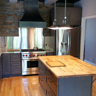 Mid-sized industrial l-shaped separate kitchen in Ottawa with a double-bowl sink, shaker cabinets, grey cabinets, stainless steel benchtops, metallic splashback, stone tile splashback, stainless steel appliances, light hardwood floors and with island.