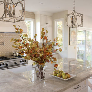 Inspiration for a large traditional u-shaped eat-in kitchen in San Francisco with a farmhouse sink, beaded inset cabinets, white cabinets, quartzite benchtops, beige splashback, porcelain splashback, stainless steel appliances, marble floors and with island.