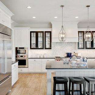Diseño de cocina comedor en U, clásica, grande, con armarios estilo shaker, puertas de armario blancas, salpicadero verde, electrodomésticos de acero inoxidable, suelo de madera clara, una isla y suelo beige