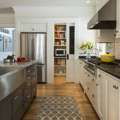 Example of a large classic l-shaped medium tone wood floor kitchen design in Portland Maine with a farmhouse sink, shaker cabinets, white cabinets, granite countertops, white backsplash, ceramic backsplash and stainless steel appliances