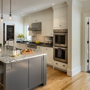 Eat-in kitchen - large traditional galley light wood floor eat-in kitchen idea in Portland Maine with a farmhouse sink, shaker cabinets, white cabinets, granite countertops, white backsplash, ceramic backsplash and stainless steel appliances