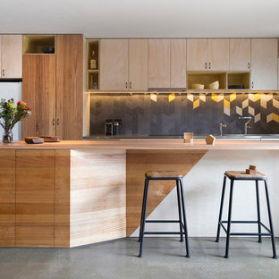 Kitchen - mid-sized contemporary galley concrete floor kitchen idea in Melbourne with flat-panel cabinets, light wood cabinets, multicolored backsplash, white appliances and an island