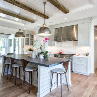 Large farmhouse galley dark wood floor open concept kitchen photo in New York with recessed-panel cabinets, white cabinets, white backsplash, subway tile backsplash, stainless steel appliances, an island and soapstone countertops