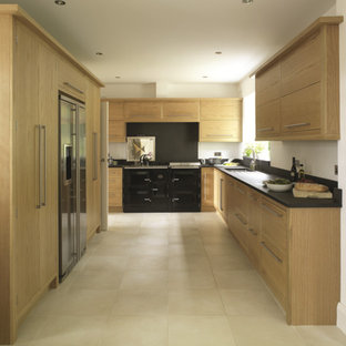 Photo of a small modern galley enclosed kitchen in Surrey with a single-bowl sink, flat-panel cabinets, medium wood cabinets, granite worktops, stainless steel appliances and no island.