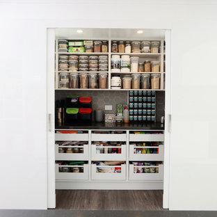 メルボルンの中くらいのモダンスタイルのおしゃれなキッチン (ダブルシンク、フラットパネル扉のキャビネット、白いキャビネット、クオーツストーンカウンター、モザイクタイルのキッチンパネル、シルバーの調理設備、クッションフロア、グレーのキッチンカウンター) の写真