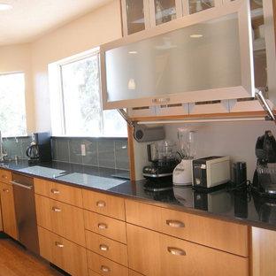 Bild på ett stort vintage kök, med en undermonterad diskho, släta luckor, skåp i mellenmörkt trä, bänkskiva i kvarts, grönt stänkskydd, stänkskydd i glaskakel, rostfria vitvaror och mörkt trägolv