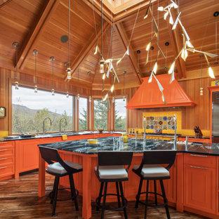 На фото: огромная кухня в стиле рустика с фасадами с декоративным кантом, оранжевыми фасадами, островом и сводчатым потолком с