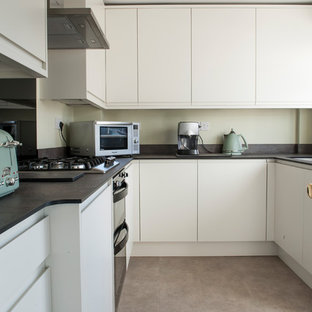 Medium sized contemporary u-shaped enclosed kitchen in Manchester with a built-in sink, flat-panel cabinets, laminate countertops, stainless steel appliances, vinyl flooring, no island and multicoloured worktops.