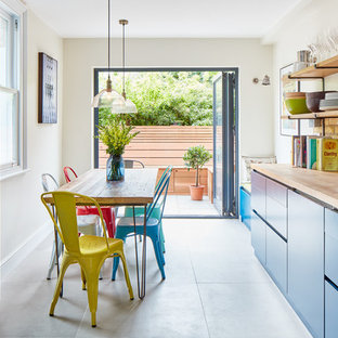 Inspiration for an eclectic kitchen/diner in London with flat-panel cabinets, blue cabinets, wood worktops, beige splashback, stainless steel appliances and no island.