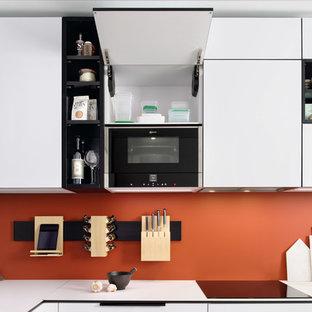 サリーの小さいモダンスタイルのおしゃれなキッチン (シングルシンク、フラットパネル扉のキャビネット、白いキャビネット、ラミネートカウンター、オレンジのキッチンパネル、シルバーの調理設備の、テラコッタタイルの床、マルチカラーの床、白いキッチンカウンター) の写真
