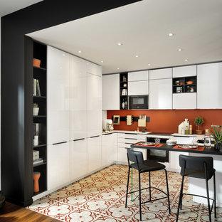 サリーの小さいコンテンポラリースタイルのおしゃれなキッチン (シングルシンク、フラットパネル扉のキャビネット、白いキャビネット、ラミネートカウンター、オレンジのキッチンパネル、テラコッタタイルの床、マルチカラーの床、白いキッチンカウンター、黒い調理設備) の写真