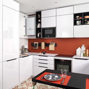 サリーの小さいモダンスタイルのおしゃれなキッチン (シングルシンク、フラットパネル扉のキャビネット、白いキャビネット、ラミネートカウンター、オレンジのキッチンパネル、シルバーの調理設備、テラコッタタイルの床、マルチカラーの床、白いキッチンカウンター) の写真