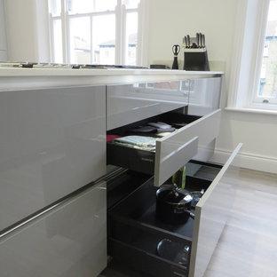 ロンドンの中くらいのコンテンポラリースタイルのおしゃれなキッチン (ドロップインシンク、フラットパネル扉のキャビネット、グレーのキャビネット、珪岩カウンター、グレーのキッチンパネル、木材のキッチンパネル、黒い調理設備、クッションフロア、グレーの床、白いキッチンカウンター) の写真