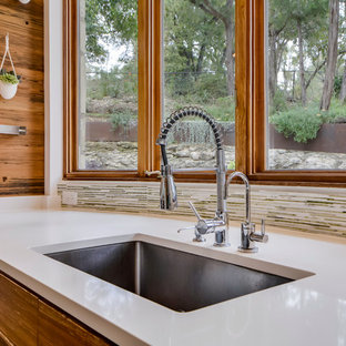 This is an example of a medium sized contemporary l-shaped open plan kitchen in Austin with a submerged sink, flat-panel cabinets, medium wood cabinets, quartz worktops, stainless steel appliances, an island and travertine flooring.
