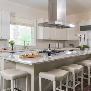 Inspiration for a large beach style l-shaped kitchen in Austin with shaker cabinets, white cabinets, beige splashback, panelled appliances, dark hardwood floors, with island, a drop-in sink, laminate benchtops, ceramic splashback and brown floor.