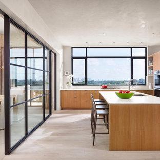 オースティンの大きいミッドセンチュリースタイルのおしゃれなキッチン (ドロップインシンク、フラットパネル扉のキャビネット、淡色木目調キャビネット、白いキッチンパネル、シルバーの調理設備、淡色無垢フローリング、白い床、白いキッチンカウンター) の写真