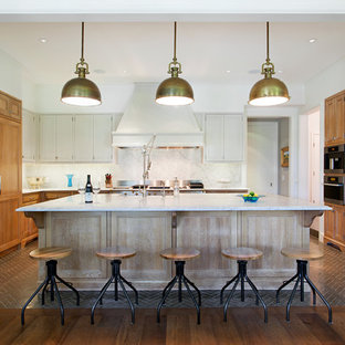 Example of a mid-sized classic u-shaped dark wood floor and brown floor open concept kitchen design in Austin with recessed-panel cabinets, medium tone wood cabinets, white backsplash, an island, quartzite countertops and stainless steel appliances