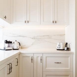 メルボルンの大きいトラディショナルスタイルのおしゃれなキッチン (アンダーカウンターシンク、シェーカースタイル扉のキャビネット、白いキャビネット、タイルカウンター、白いキッチンパネル、磁器タイルのキッチンパネル、シルバーの調理設備の、無垢フローリング、茶色い床、白いキッチンカウンター) の写真