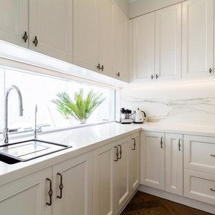 メルボルンの大きいトラディショナルスタイルのおしゃれなキッチン (アンダーカウンターシンク、シェーカースタイル扉のキャビネット、白いキャビネット、タイルカウンター、白いキッチンパネル、磁器タイルのキッチンパネル、シルバーの調理設備、無垢フローリング、茶色い床、白いキッチンカウンター) の写真