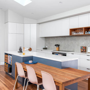 Photo of a contemporary l-shaped eat-in kitchen in Canberra - Queanbeyan with an undermount sink, flat-panel cabinets, white cabinets, grey splashback, cement tile splashback, panelled appliances, medium hardwood floors, an island, brown floor and white benchtop.