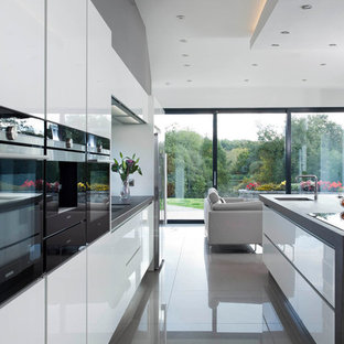 Design ideas for a large contemporary single-wall open plan kitchen in Belfast with an integrated sink, flat-panel cabinets, white cabinets, engineered stone countertops, grey splashback, stone slab splashback, stainless steel appliances, porcelain flooring and an island.