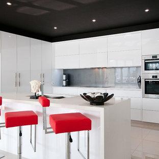 ゴールドコーストの広いモダンスタイルのおしゃれなキッチン (アンダーカウンターシンク、フラットパネル扉のキャビネット、白いキャビネット、クオーツストーンカウンター、グレーのキッチンパネル、ガラス板のキッチンパネル、シルバーの調理設備、セラミックタイルの床) の写真