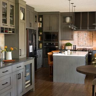 Стильный дизайн: огромная п-образная кухня в стиле современная классика с обеденным столом, врезной раковиной, серыми фасадами, столешницей из кварцевого композита, фартуком из плитки кабанчик, черной техникой, островом, фасадами в стиле шейкер, темным паркетным полом, коричневым полом и белой столешницей - последний тренд