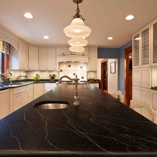 Inspiration for a large farmhouse u-shaped kitchen/diner in Philadelphia with a submerged sink, recessed-panel cabinets, white cabinets, soapstone worktops, white splashback, ceramic splashback, integrated appliances, lino flooring and an island.