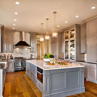 Design ideas for a large traditional u-shaped eat-in kitchen in Portland with a farmhouse sink, recessed-panel cabinets, quartz benchtops, subway tile splashback, panelled appliances, medium hardwood floors, with island, beige cabinets, grey splashback and brown floor.