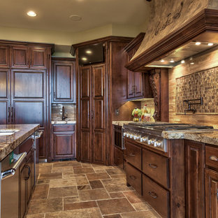 Large mediterranean l-shaped open plan kitchen in Omaha with a double-bowl sink, raised-panel cabinets, dark wood cabinets, granite benchtops, beige splashback, stone tile splashback, stainless steel appliances, slate floors, with island and beige floor.