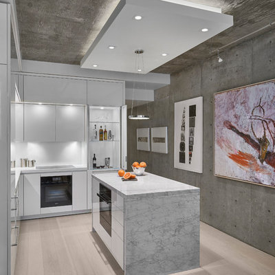 Small trendy l-shaped light wood floor and beige floor kitchen photo in Chicago with white cabinets, white backsplash, an island, flat-panel cabinets, black appliances and white countertops