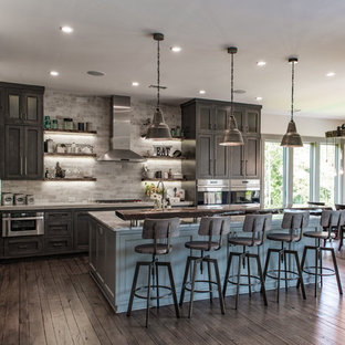 Large mountain style l-shaped brown floor and dark wood floor eat-in kitchen photo in Charleston with shaker cabinets, stainless steel appliances, an island, dark wood cabinets, a farmhouse sink, quartzite countertops, gray backsplash and stone tile backsplash