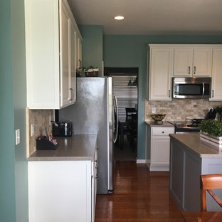 Mid-sized transitional u-shaped eat-in kitchen in Indianapolis with an integrated sink, shaker cabinets, white cabinets, solid surface benchtops, beige splashback, travertine splashback, stainless steel appliances, medium hardwood floors, with island, brown floor and beige benchtop.