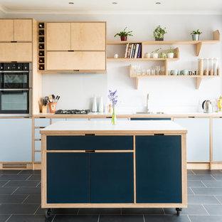 Idee per una cucina design di medie dimensioni con top in legno, paraspruzzi bianco, paraspruzzi con lastra di vetro, elettrodomestici in acciaio inossidabile, isola, top grigio, lavello da incasso, ante lisce, ante blu e pavimento nero