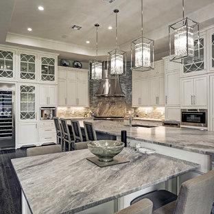ヒューストンの巨大なエクレクティックスタイルのおしゃれなキッチン (ガラスカウンター、マルチカラーのキッチンパネル、ガラスタイルのキッチンパネル、アンダーカウンターシンク、シェーカースタイル扉のキャビネット、白いキャビネット、パネルと同色の調理設備、濃色無垢フローリング、黒い床) の写真