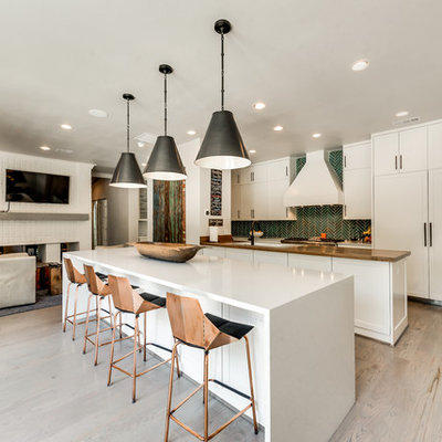 Example of a trendy single-wall light wood floor and brown floor open concept kitchen design in Dallas with a double-bowl sink, shaker cabinets, white cabinets, solid surface countertops, green backsplash, ceramic backsplash, stainless steel appliances and two islands