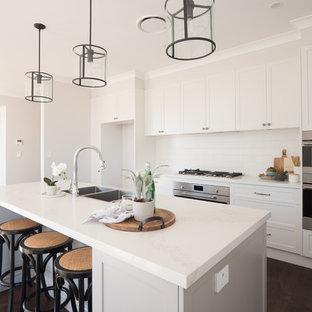 シドニーの中サイズのシャビーシック調のおしゃれなキッチン (ダブルシンク、シェーカースタイル扉のキャビネット、グレーのキャビネット、人工大理石カウンター、白いキッチンパネル、セラミックタイルのキッチンパネル、シルバーの調理設備の、濃色無垢フローリング、茶色い床、白いキッチンカウンター) の写真