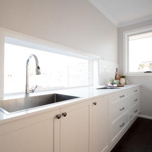 シドニーの中サイズのシャビーシック調のおしゃれなキッチン (ダブルシンク、シェーカースタイル扉のキャビネット、グレーのキャビネット、人工大理石カウンター、白いキッチンパネル、セラミックタイルのキッチンパネル、シルバーの調理設備、濃色無垢フローリング、茶色い床、白いキッチンカウンター) の写真
